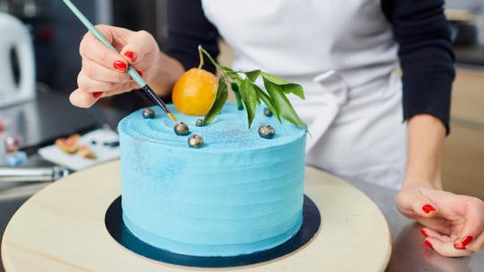 Kobieta dekoruje pędzelkiem niebieski tort.. Czysty perfekcjonizm.