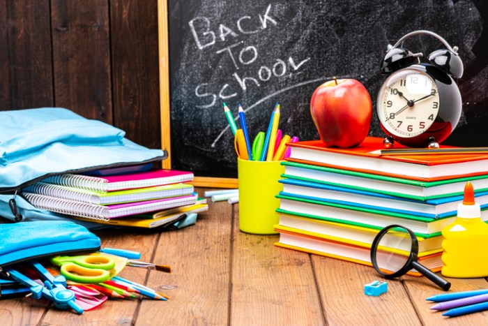 Back to school: multicolored school supplies shot on wooden desk.