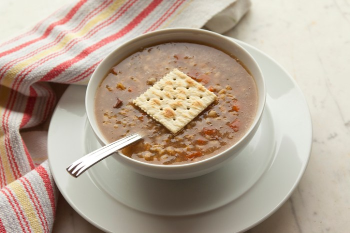 Bowl of vegetarian barley soup with a salt cracker garnish in a white bowl with saucer on a white marble table