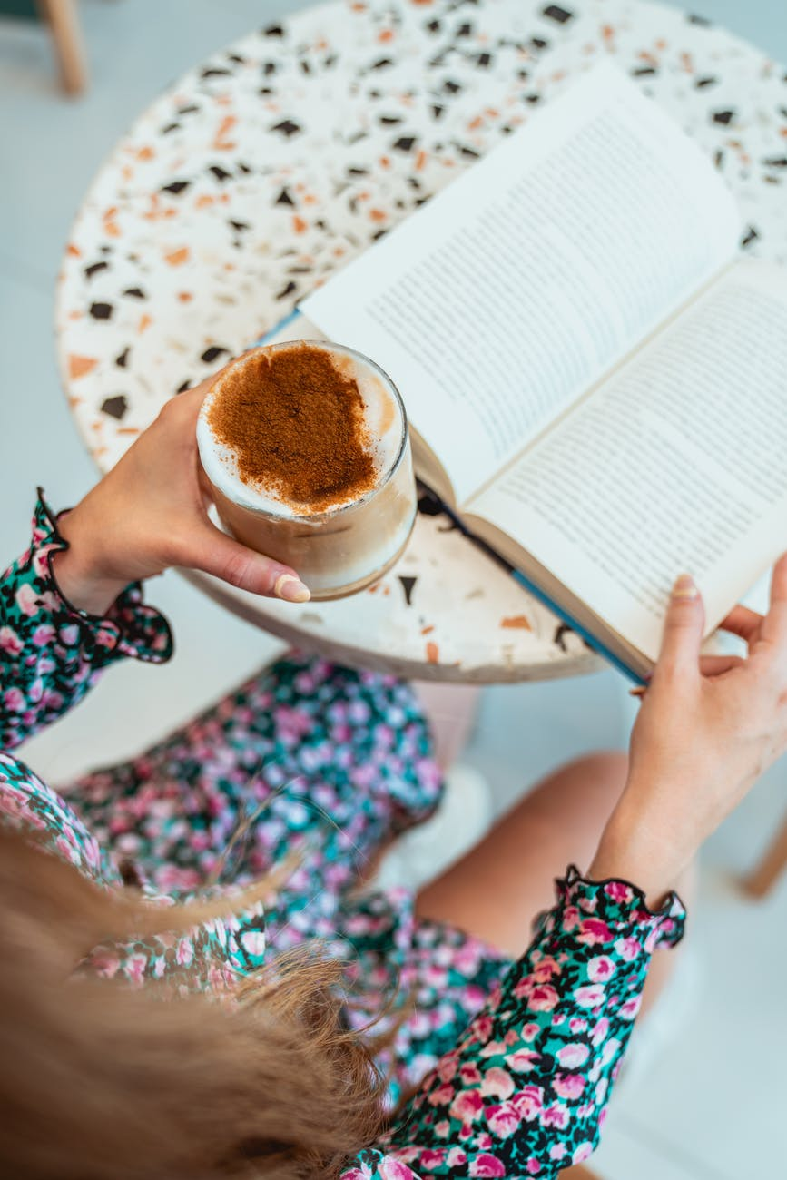 photo of woman reading book while holding iced latte