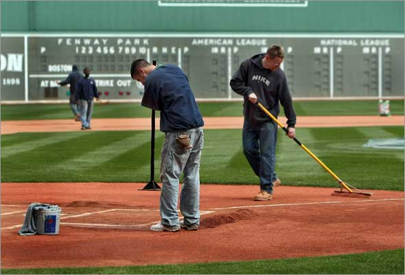 The season opener at Fenway Park might be a washout on Monday, but groundscrew members John Driscoll pounds down the dirt around homeplate while Jeremy Fuller smooths the gravel in the the area on Saturday morning.