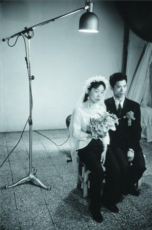 1980年,上海照相馆,身着半身婚纱的新婚夫妇。为了省钱,新娘只租了西式婚纱的上半身。