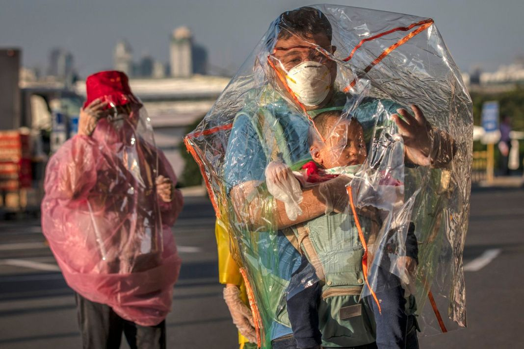 Travelers wore raincoats, plastic covers, gloves, goggles, and facemasks as they wait for their flight at Ninoy Aquino International Airport on Wednesday in Manila, Philippines.