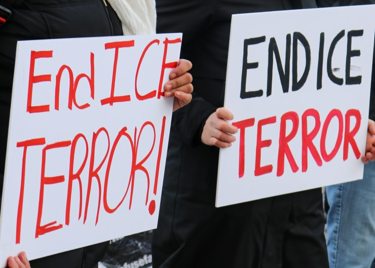 "Photo with two signs in black and red reading ""End ICE Terror"""