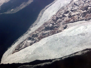 Spit of productively farmed land surrounded by sea ice
