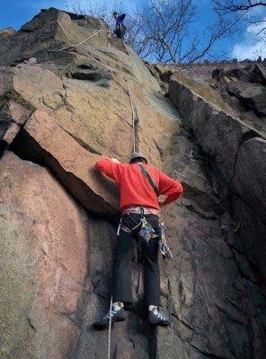 Reaching the crux of a rock climb, an activity with high hazard.