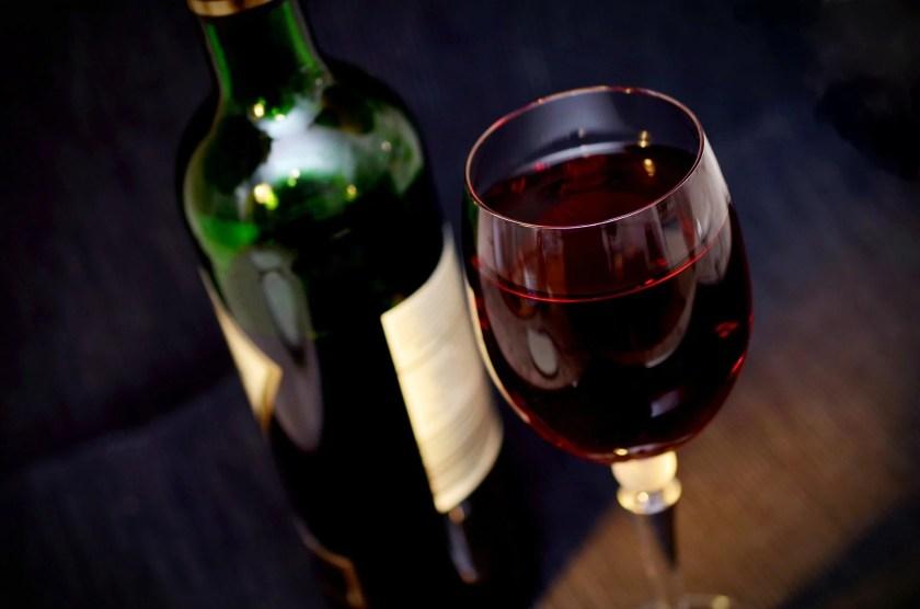 Rotweinflasche hinter einem gefüllten Weinweinglas