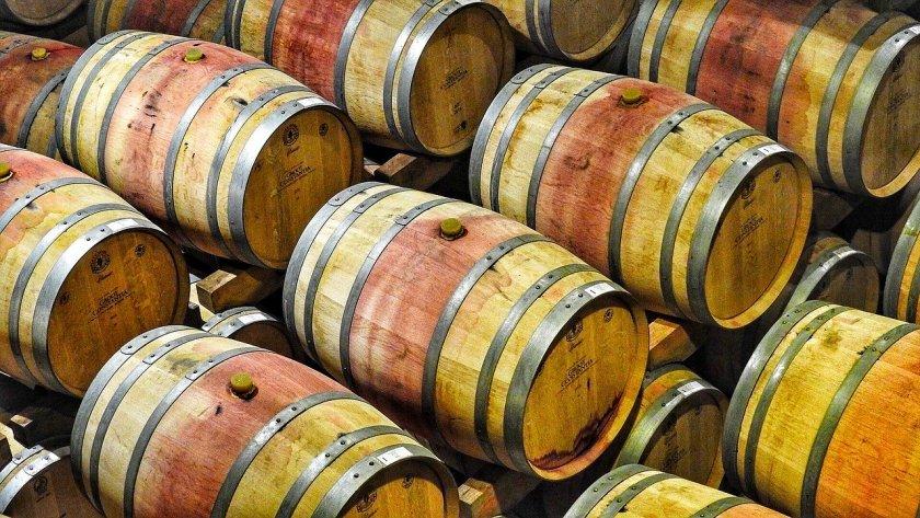 Weinkeller mit vielen aufeinander gestapelten Barrique-Fässern