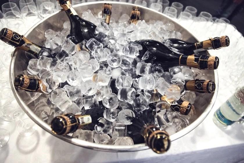 Champagnerschale mit Eiswürfeln und Sektflaschen