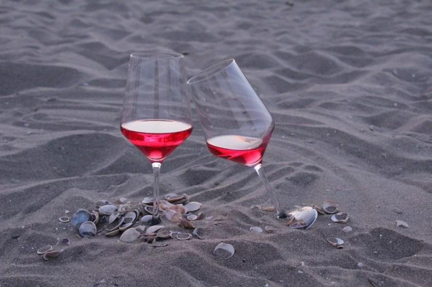 Weingläser mit Rosé gefüllt am Strand zwischen Muscheln
