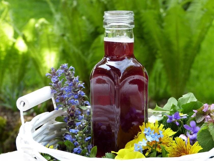 Rotweinessig in einem Korb voller Blumen