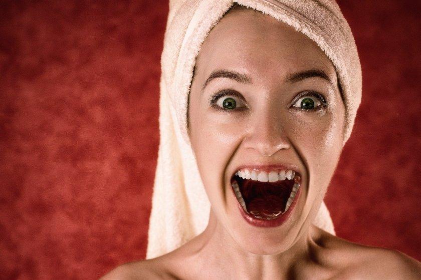 Frau mit freudig aufgerissenem Mund und sehr schönen Zähnen