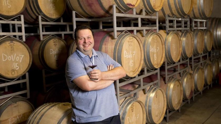 Winzer Walter Glatzer im Weinkeller mit einem Glas Rotwein in der Hand.