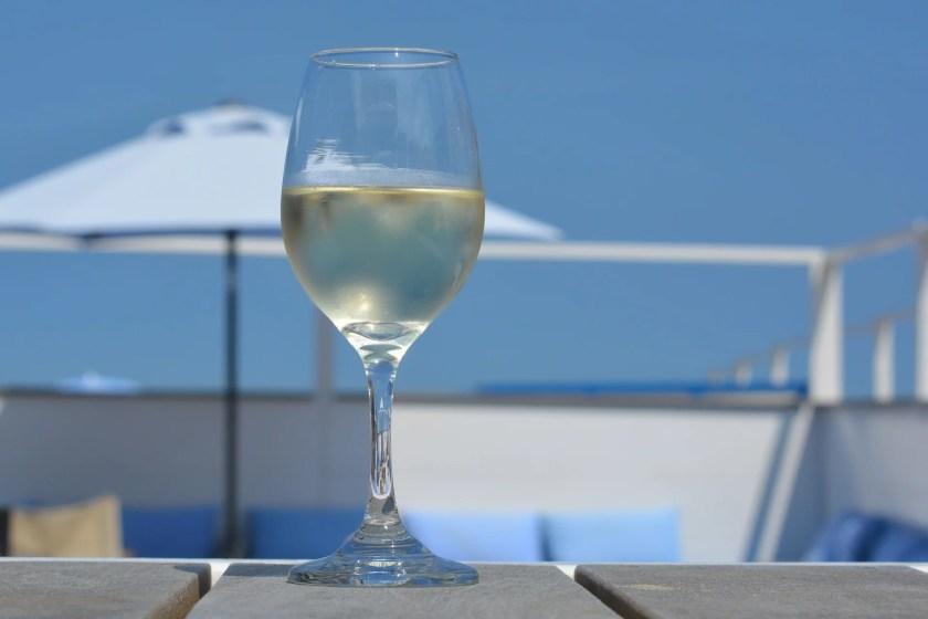 Eine Dachterrasse, auf der ein Glas mit Weißwein steht.
