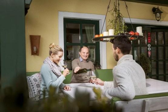 Winzer Manfred Edelmann bei einer Weinprobe mit zwei Gästen