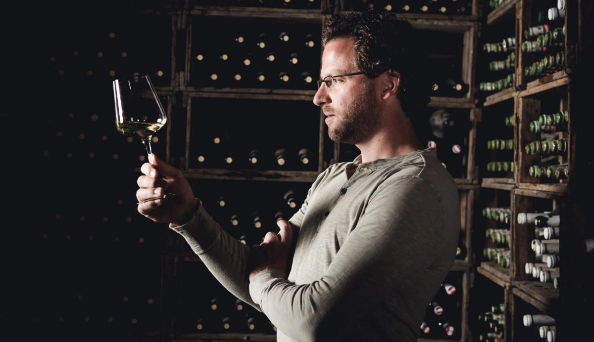 Winzer Wolfgang Maitz im Weinkeller mit einem Glas Sauvignon Blanc in der Hand.