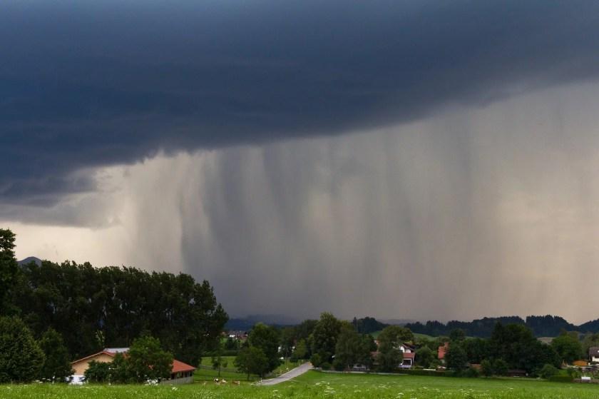 Starker Regenfall aus Gewitterwolken über einem Dorf.