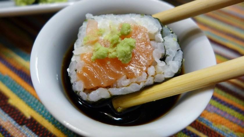 Ein Maki-Sushi mit Wasabi wird in ein Schälchen mit Sojasoße getunkt.