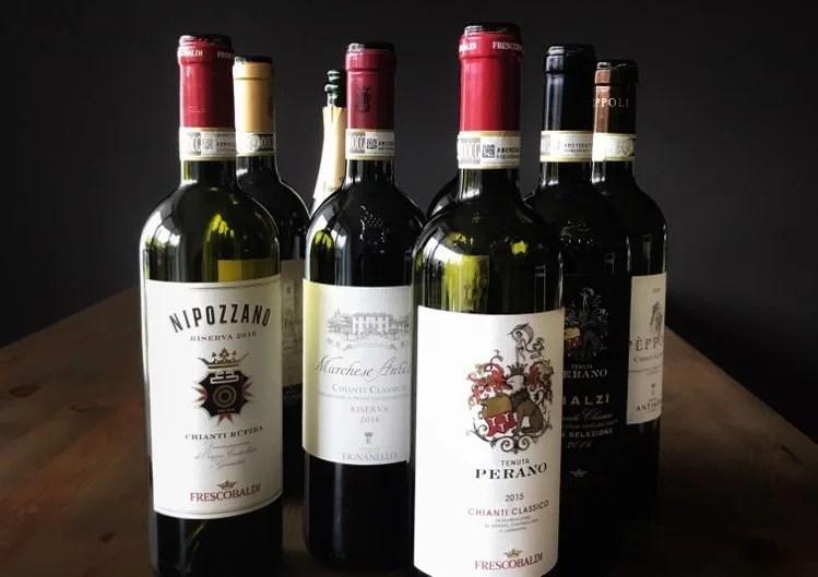 Unterschiedliche leere Flaschen Chianti Classico auf einem Tisch vor schwarzen Hintergrund
