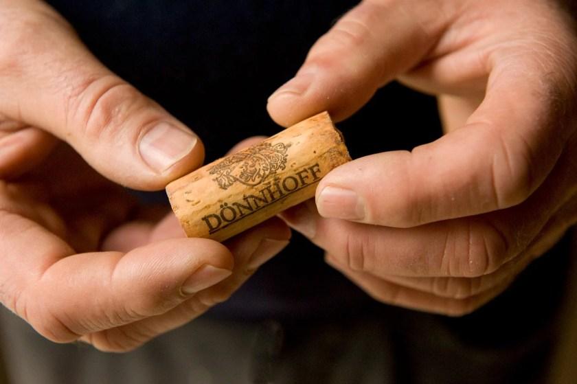 Zwei Hände in Nahaufnahme die einen Korken vom Weingut Dönnhoff halten