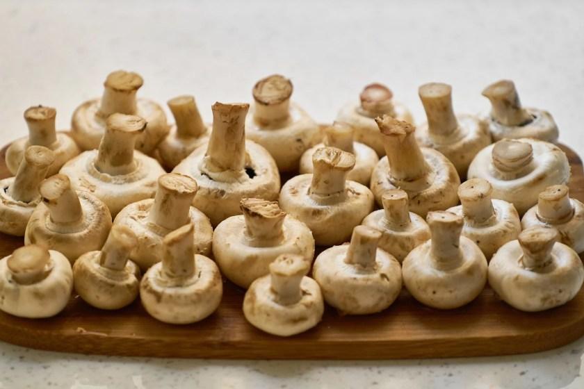 Viele kleine weiße Champignons kopfüber auf einem Holzbrett