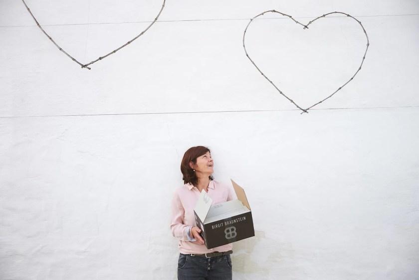 Winzerin Birgit Braunstein vor einer weißen Wand, wie sie zu einem Herz aus Stacheldraht hochguckt.