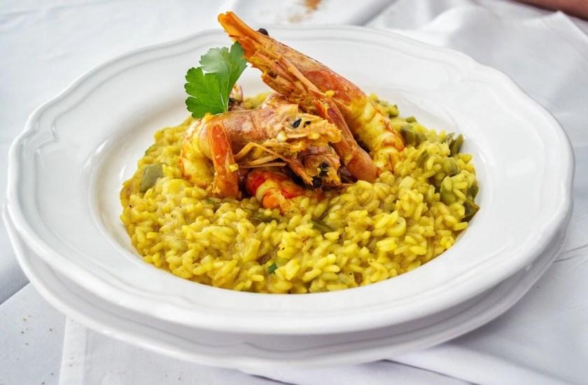 Weißer Teller mit gelben Risotto, auf dem drei Garnelen und etwas glatte Petersilie drapiert sind