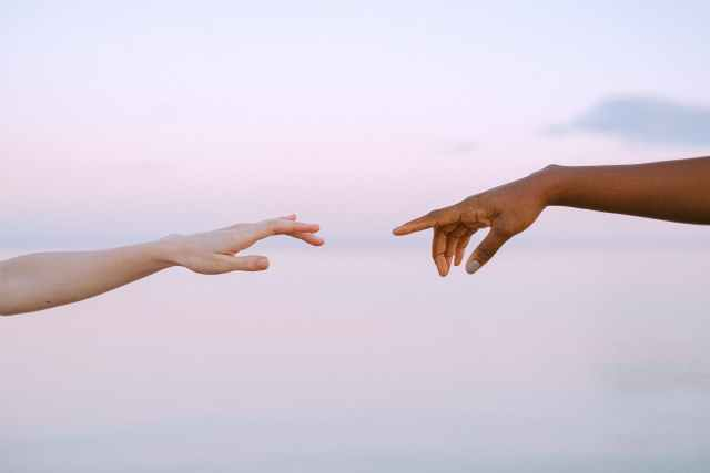 photo of people reaching for each others hands