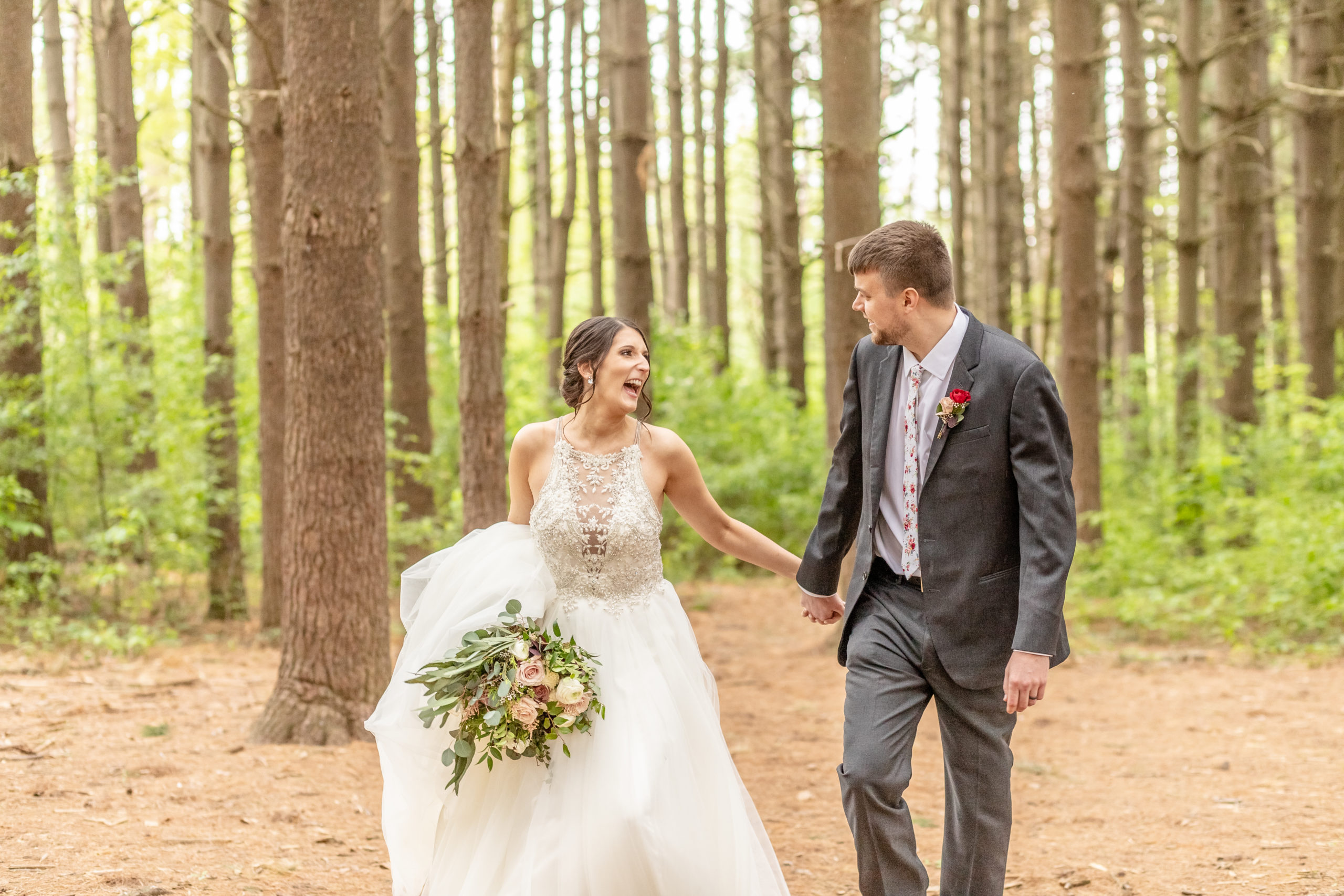 bride and groom, halter neck wedding dress, bouquet, grey suit, red rose boutonniere, laughing