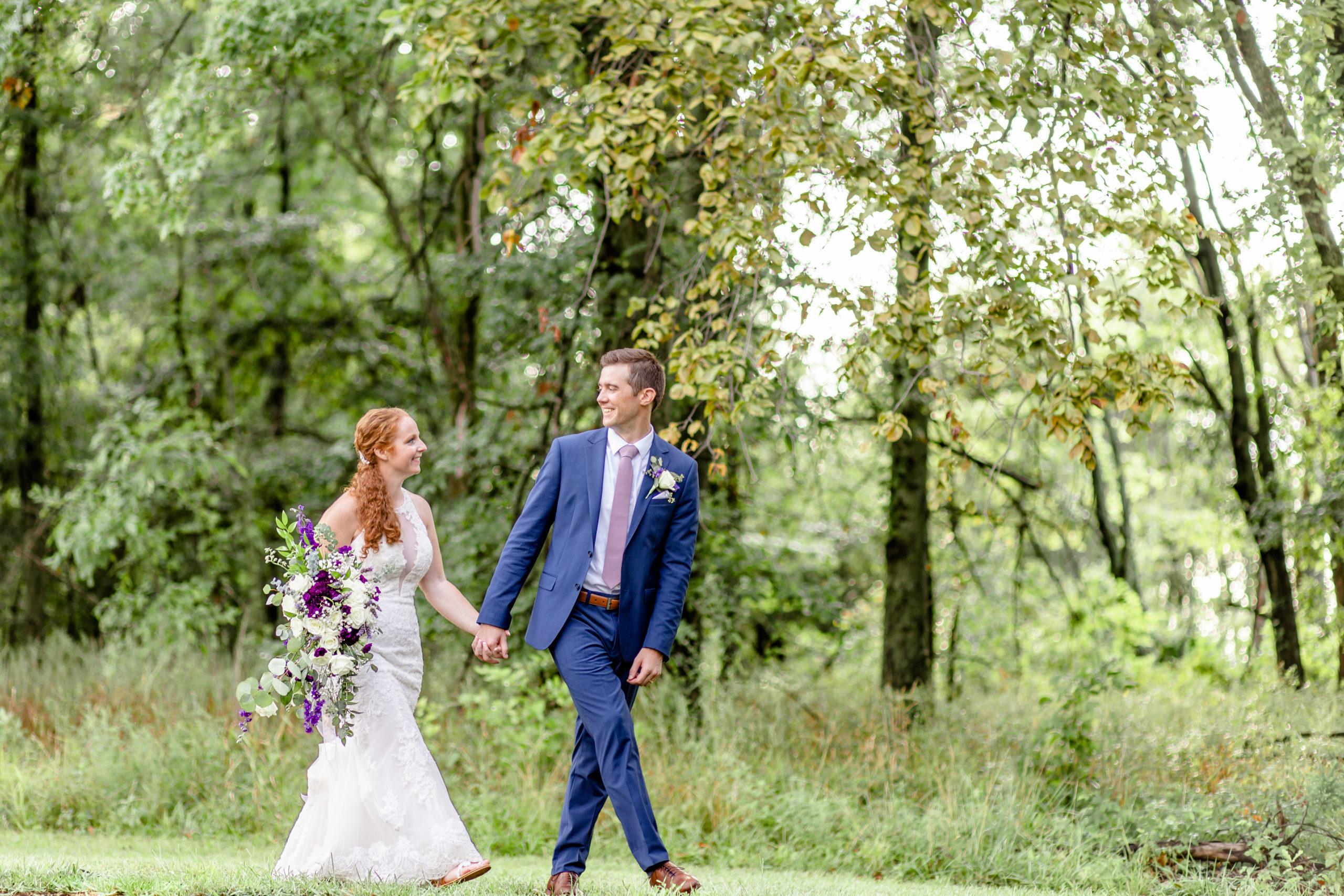 bride and groom walking, lakeside wedding, woodland wedding, southern illinois wedding photography, blue and purple wedding, white lace wedding dress, purple wedding bouquet