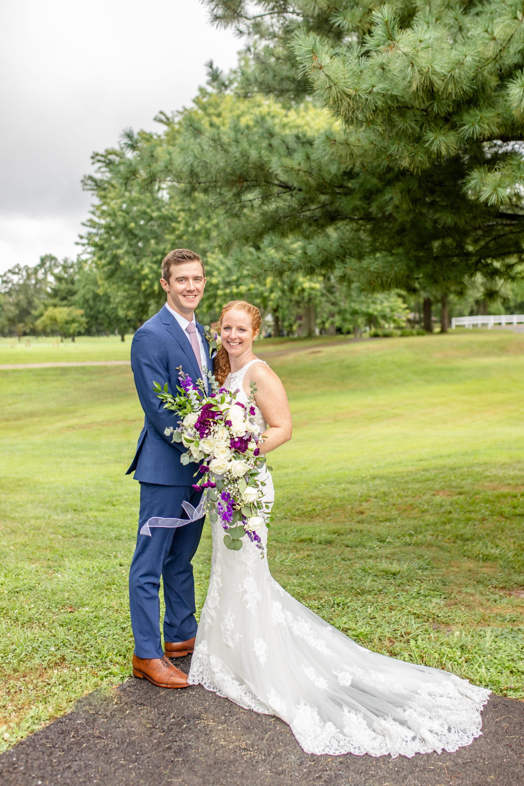 lakeside wedding, woodland wedding, lace wedding dress, blue tuxedo, bride and groom embracing, purple bouquet, purple wedding bouquet