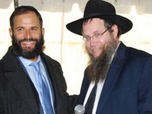 Rabbi Moshe Scheiner congratulates Rabbi Pesach Scheiner on the groundbreaking.