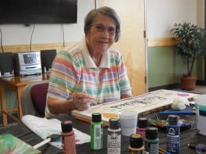Golden West resident, Dolly, paints a sign for the farm.