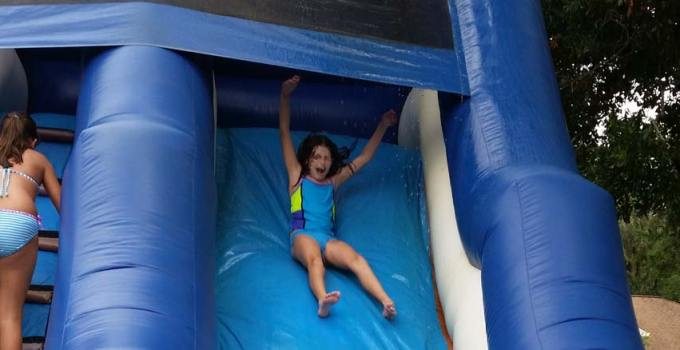Dolphin waterslide rental wiht girl sliding down in Port Orange Florida