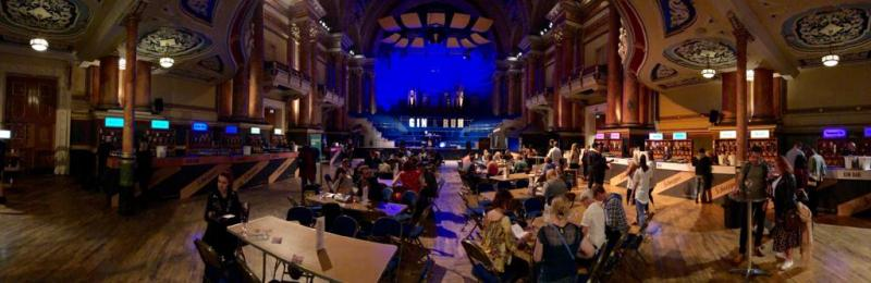 "Town hall filled with tables, with a bar around the edge of the room. There's a sign saying ""gin"" & ""rum"" at the back."