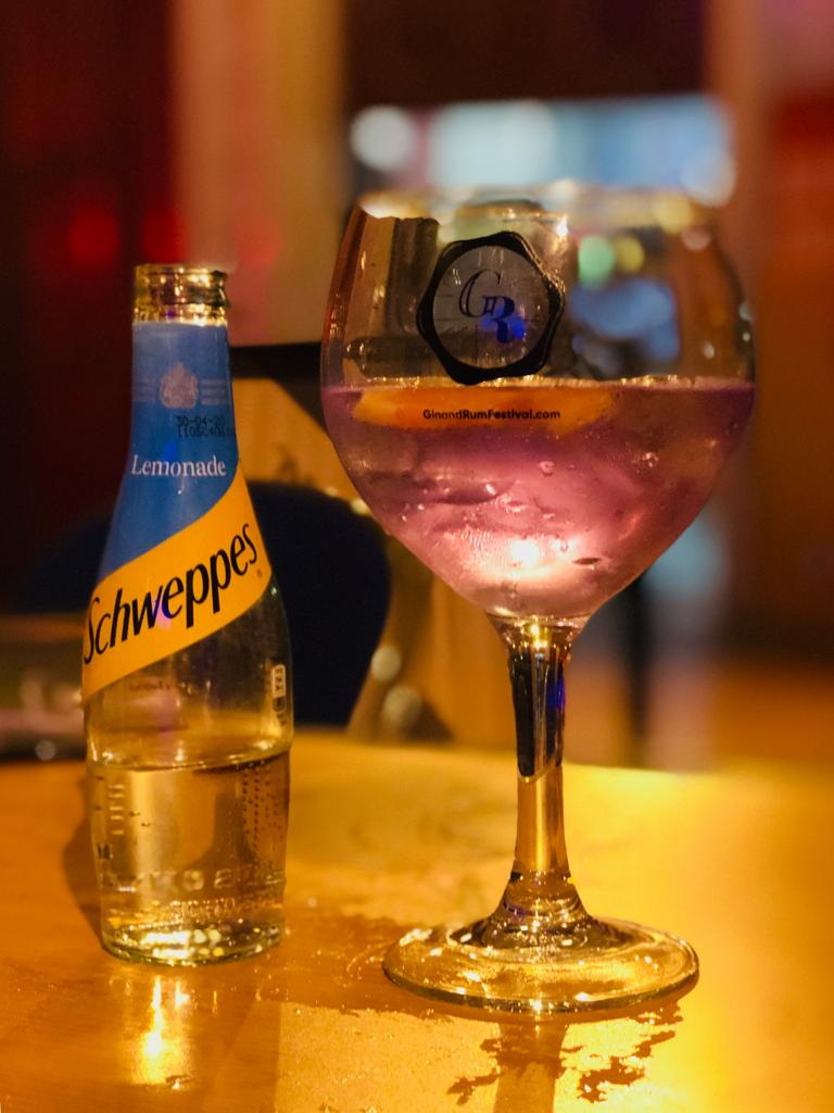a gin glass with a pink gin (empress gin) in it, next to a schweppes lemonade bottle