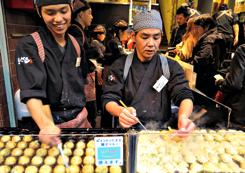 Preparing takoyaki in Osaka. You Have To Eat These Dishes in Osaka, by Boutique Japan.