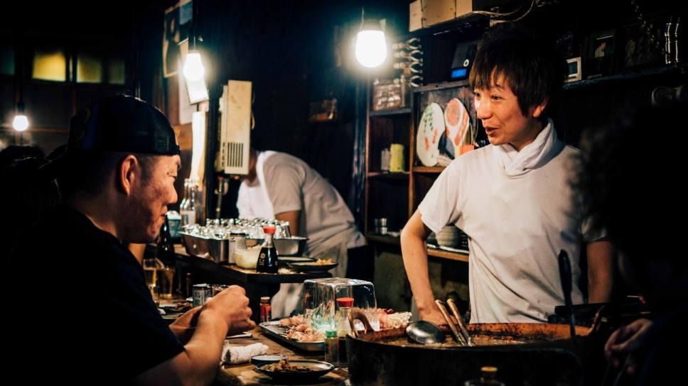 Chef and diner at a casual izakaya, or tavern, in Japan