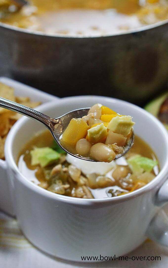 A white mug filled with white bean turkey chili. There's a spoonful of chili ready to take a bite!