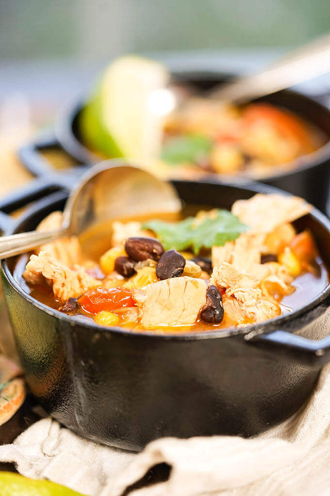 Crock Pot Chicken Taco Soup in black cast iron bowl with spoon.
