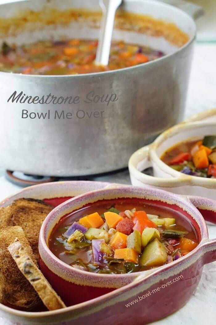 The best Minestrone Soup Recipe! Two bowls filled with soup with homemade toast points. There is also a pot of soup with a ladle ready to serve up seconds!