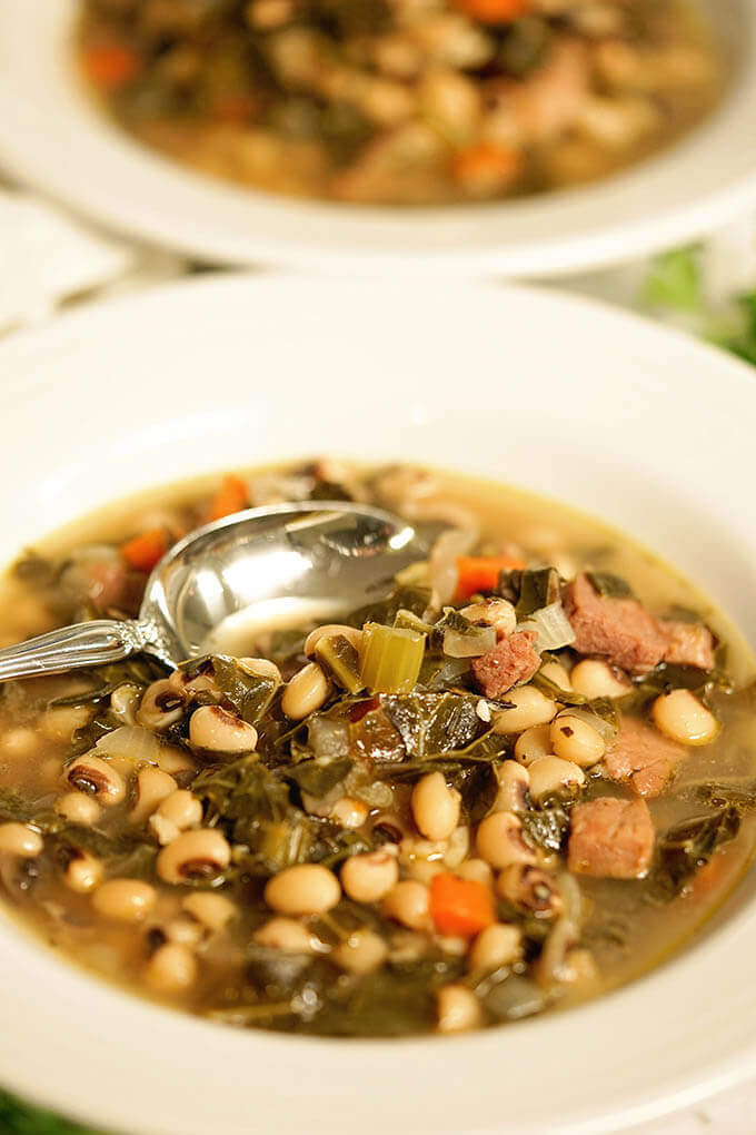 A white bowl filled with black eyed pea soup with ham.