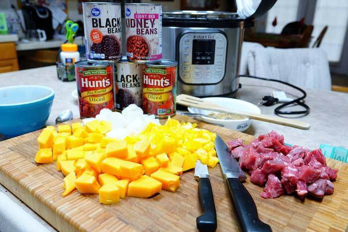 All the ingredients for butternut squash chili, diced squash and onions, stew meat and cans of beans and tomatoes stacked int he background with the Instant Pot ready to use.