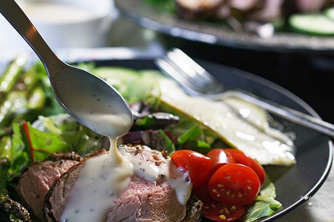 Pork Tenderloin Salad with creamy vinaigrette drizzled over the top.