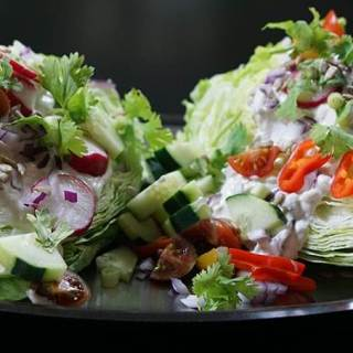 Two slices of wedge salad on silver platter.