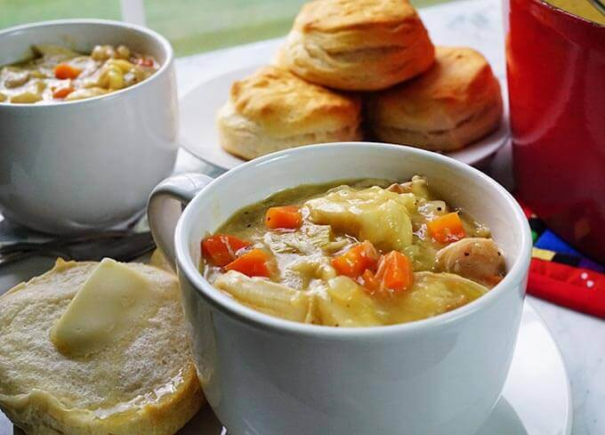 Mugs of homemade chicken and dumpling soup with a buttered biscuit. There are more biscuits to pass along with extra helpings of soup!