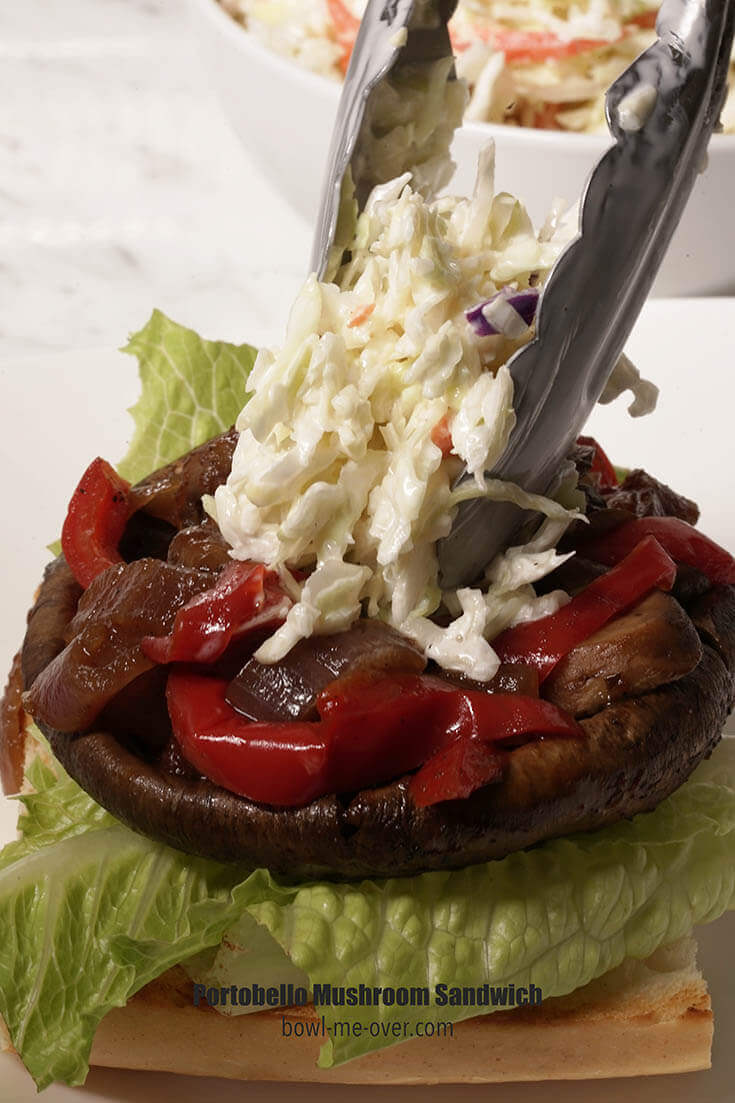 A burger bun topped with lettuce, portobello mushroom, onions and peppers. There's a spoonful of coleslaw being placed on the top.