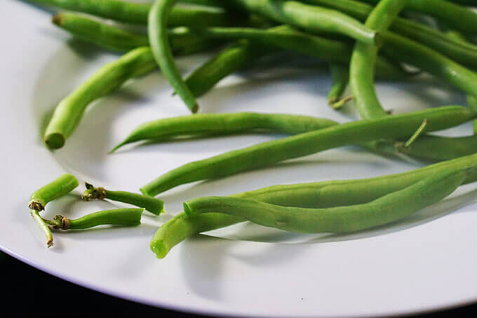 A white plate filled with green beans. The ends have been snapped off some of the greens.