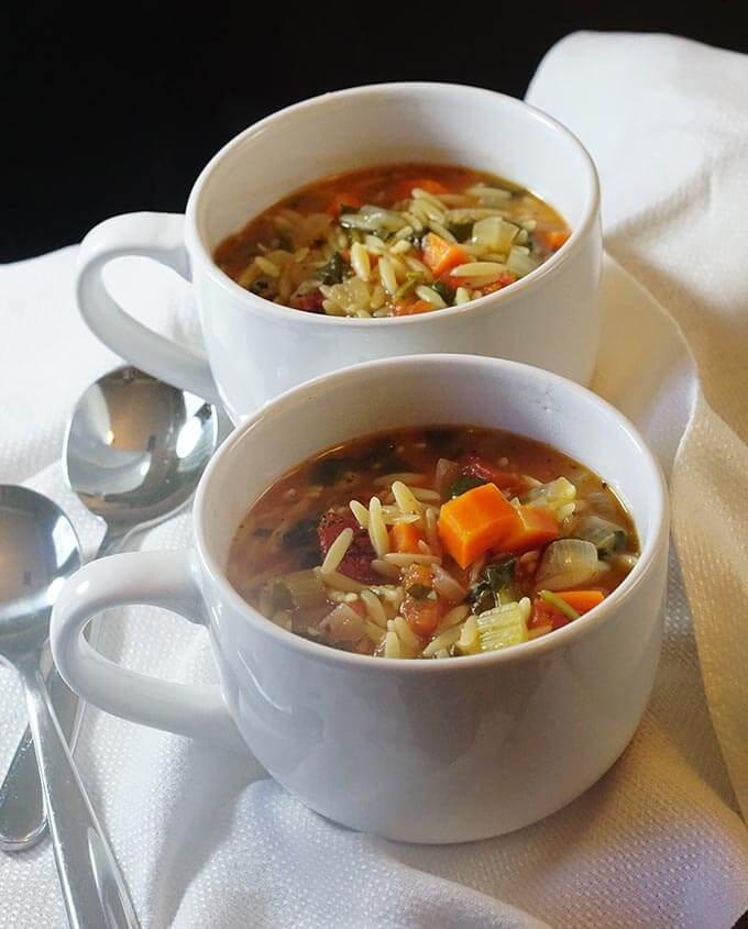 Two white bowls filled with vegetable orzo soup on a white cloth with spoons for serving.