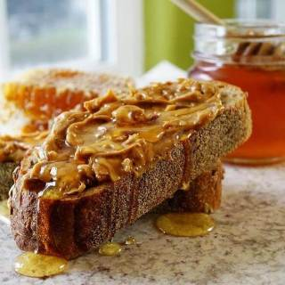 Thick slices of bread spread with chunky peanut butter topped with drizzles of honey.